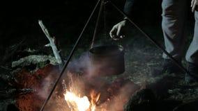 natt för småskogcampfireförbränning Mannen sätter kitteln på brand arkivfilmer