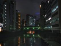 Natt i futuristisk stad med floden och skyskrapor royaltyfri foto
