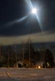 Natt och drevstation som täckas med insnöat månskenet horisont för natt för stadseps-jpg Royaltyfria Bilder