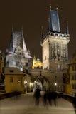 Natt snöig färgrika Prague Lesser Town med domkyrkan för brotorn- och St Nicholas ` från Charles Bridge, Tjeckien Royaltyfria Bilder