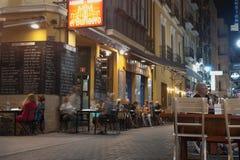 Natt som äter middag i den Spanien gatan och byggande sc Royaltyfri Fotografi