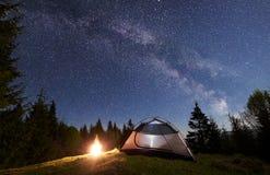 Natt som campar i berg Turist- tält vid lägereld nära skog under blå stjärnklar himmel, mjölkaktig väg arkivfoto
