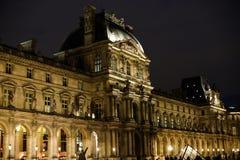 Natt som förbluffar Louvre och turister som går i Paris, Frankrike arkivbild