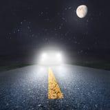 Natt som kör på en asfaltväg in mot billyktorna Arkivbild