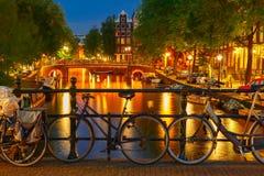 Nattbelysning av den Amsterdam kanalen och bron Arkivfoton