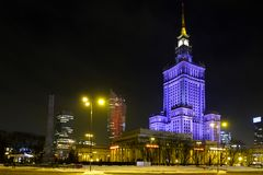 Nattbelysning av kultur- och vetenskapsslotten och seglar den Zlota 44 skyskrapan vid den Defilad fyrkanten i Warszawacentrum Arkivfoton