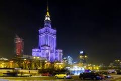 Nattbelysning av kultur- och vetenskapsslotten och seglar den Zlota 44 skyskrapan vid den Defilad fyrkanten i Warszawacentrum Arkivbild