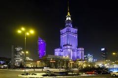 Nattbelysning av kultur- och vetenskapsslotten och seglar den Zlota 44 skyskrapan vid den Defilad fyrkanten i Warszawacentrum Arkivbilder