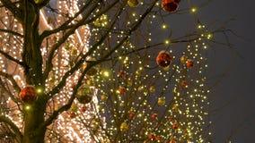 Nattbelysning i jul med de girlandfyrkanten och bollarna på träden lager videofilmer