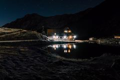 Nattberglandskap med det upplysta blåa tältet Bergmaxima och månen utomhus- på Lacul Balea sjön, Transfagarasan, royaltyfria foton