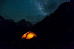 Nattberglandskap med det upplysta tältet royaltyfria foton