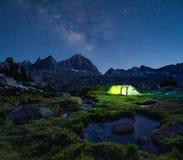Nattberglandskap med det upplysta tältet Arkivbilder