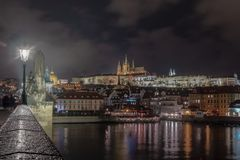 Nattbild av den Prague slotten från den Charles bron med floden i förgrunden royaltyfria foton