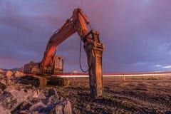 Nattbild av en hydraulisk hammare i arbetena av utvidgning av en väg royaltyfri bild