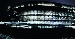 Nattbild av en upplyst byggnad i en stad royaltyfri foto