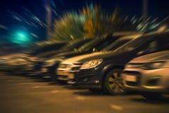 Nattbilparkering i rader, sidosikt suddighet abstrakt bakgrund Arkivfoton