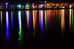 Nattblixt och skinande strand med färgrika ljus och härlig lång reflexion arkivbild