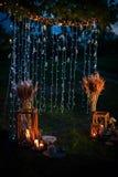 Nattbröllopceremoni med många ljus, stearinljus, lyktor Härliga romantiska glänsande garneringar i skymning royaltyfri foto