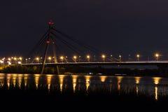 Nattbro med ljus som reflekterar i flodvatten Arkivfoton