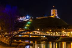 Nattcityscape av Vilnius Gediminas `-torn, Neris River, Mindaugas `-bro fotografering för bildbyråer