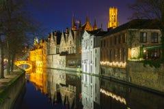 Nattcityscape med Belfort och den gröna kanalen i Bruges Royaltyfri Fotografi