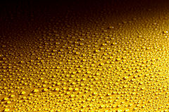 Natte gele metaaloppervlakte met het glinsteren dalingen Stock Afbeelding