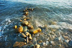 Natte overzeese rotsen, die door de golven worden gewassen Stock Foto