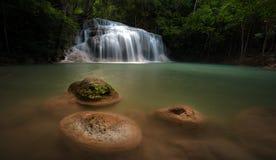 Natte stenen in rivierstroom in wild regenwoud met waterval Stock Foto