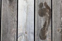 Natte voetafdrukken op een houten pier/een brug stock afbeelding