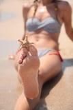 Natte vrouwelijke voeten op het strand en het zand Royalty-vrije Stock Foto's