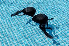 Natte vrouwelijke zwempakbustehouder of brassière die in water van zwembad drijven royalty-vrije stock afbeeldingen