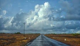 Natte weg met donkere wolken tijdens moesson stock fotografie