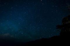 Nattetid med stjärnor i himmel Arkivbild