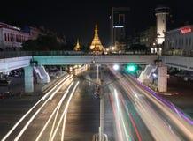Nattetid och hastighet av ljus av den guld- oktogon av den Sule pagoden p? kvadratfotplanskilda korsningen p? tv?rgatan av Anawra royaltyfria bilder