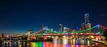 Nattetidpanorama av den Brisbane staden med purpurfärgade ljus på berättelse Arkivfoto