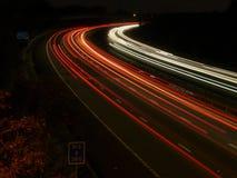 Nattetidtrafikljusslingor på motorwayen Arkivbild