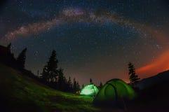 Nattfoto i bergen Tält i röjningen under den stjärnklara himlen, den mjölkaktiga vägen till den hela himlen ovanför tälten arkivbilder