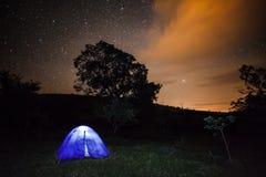 Nattfotografi - ett campa tält under stjärnklar himmel Fotografering för Bildbyråer