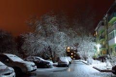 Nattgården i staden i ljuset av lyktorna, när in sen vår snöavverkningen på de gröna sidorna av träden arkivfoto