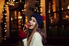 Nattgatastående av en le härlig stickande godisrotting för ung kvinna Dam som bär klassisk vinter stucken kläder Royaltyfri Foto