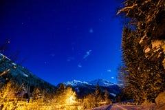 Natthimmel i fjällängarna med snö Arkivfoto