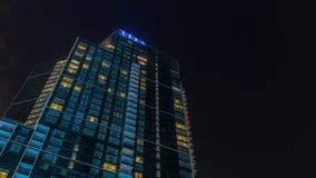 Natthimmel med moln ovanför modern skyskrapa med glödande fönsterarkitekturtimelapse arkivfilmer