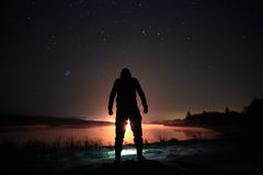 Natthimmel ovanför sjön med mans kontur Arkivfoton