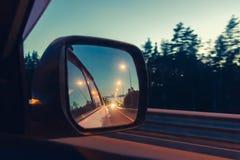 Natthuvudväg i sidospegeln, medan köra - foto, bild slapp fokus royaltyfri fotografi