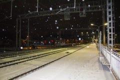 Nattjärnvägsstation snowfall Ljusen av staden i bakgrunden arkivfoton