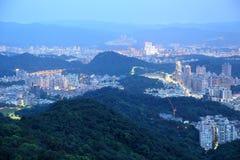 Nattlandskap av den överbefolkade Taipei staden med sikt av härliga ljus som sänder ut från byggnader Arkivfoto