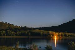 Nattlandskap med campa brasa- och stjärnahimmel, floden och berg, natt som fiskar begreppet, lägereld arkivfoto
