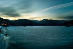 Nattlandskap med den djupfrysta sjön och berg under himlen Arkivbild