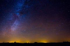 Nattlandskap med den färgrika mjölkaktiga vägen och gult ljus i horisonten arkivbild