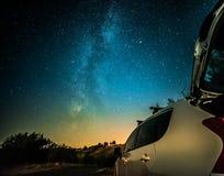 Nattlandskap med den mjölkaktiga vägen och bilen fotografering för bildbyråer